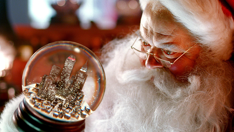 Inspiriert durch Coca-Cola, schüttelt Santa Claus vorsichtig die Schneekugeln